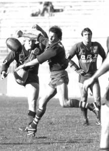 'The Angry Ant' Ross Henrick, playing for Valleys, charges down a kick by Wests Mark Crear at Lang Park, with Norm Carr in the background.